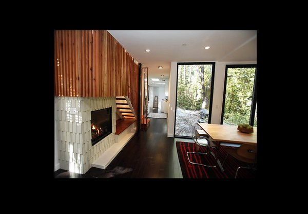 The interior metal grating motif is continued in these stairs made out of redwood from a tree on-site. A centrally-located gas fireplace distributes heat evenly throughout the home as an energy-saving measure.