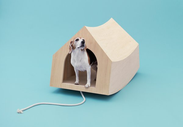 """Dutch architects MVRDV were assigned the beagle, a """"curious and playful"""" breed the firm thought should have some power of its own. An optional cord attached to the portable birch plywood structure means Fido can use the entire thing as a pull toy. At rest, the pooch palace riffs on the traditional Snoopy-esque doghouse silhouette with its simple interior and gabled roof; at play, it becomes a see-saw reminiscent of MVRDV's own Balancing Barn."""