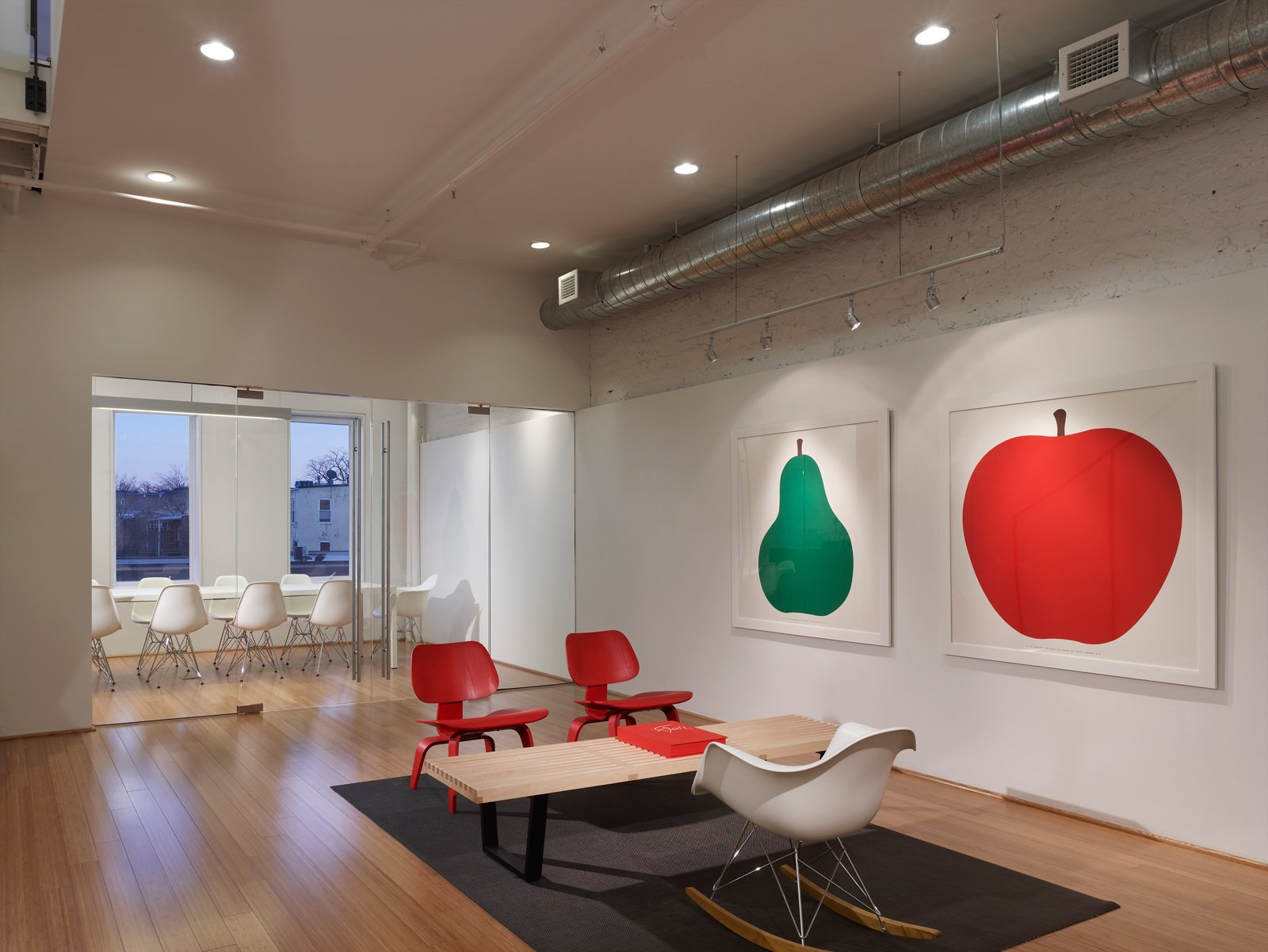 """Red, green, and white reduce the visual clutter of the office. The conference room gets plenty of natural light and the wall, coated with Idea Paint (TM) is used for brainstorming project ideas. """"We get a lot of natural light. Light is really important to me, personally. I don't perform well when I'm in a dark, enclosed space. We wanted to keep it really clean because we deal with color all day long,"""" says Pum. Photo by: Anice Hoachlander of Hoachlander Davis Photography  Photo 4 of 9 in Design Army, Washington, D.C."""
