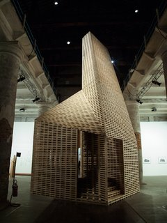 From Arsenale: Exploring the links between timber and brickwork, the Irish architects Sheila O'Donnell and John Tuomey present Vessel, a wooden structure (passage, chamber, and funnel) in raw dialogue with the layered brick construction of the site, the historic Arsenale. Shipbuilding and archaic constructions are thus re-examined.
