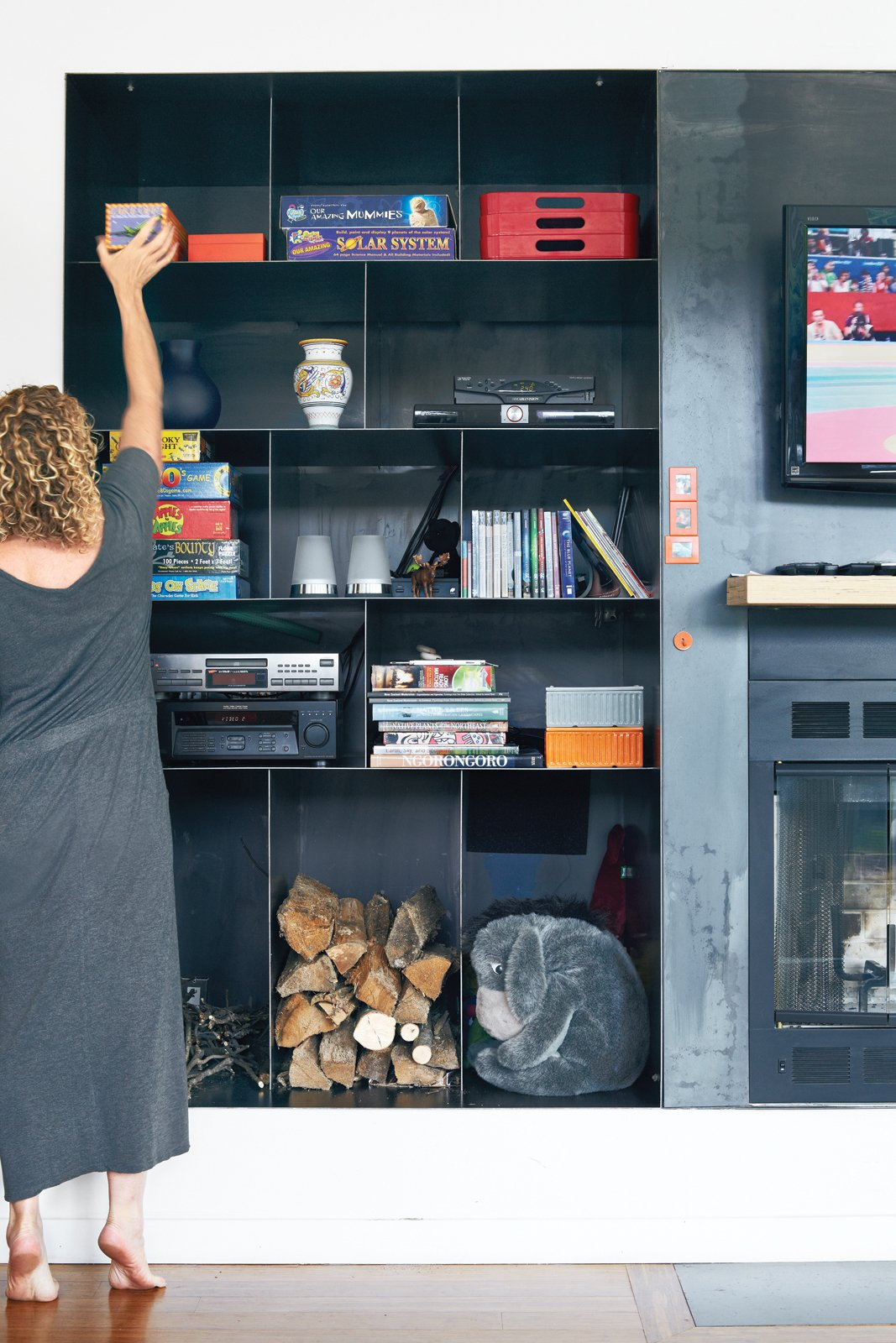 "Three-For-One: Gibbs says the custom hot-rolled black steel storage unit in the living space's one exterior wall was the architects' ""baby."" Having only one unit to house a television, a fireplace, and wood storage was a top priority. Even in the ""baking hot"" summer months, she says, ""My son wants to roast marshmallows.""  monessenhearth.com  Photo 1 of 9 in The New Zealand Native Who Can't Get Enough of the Garden State"