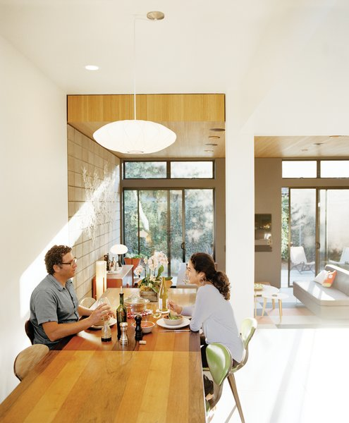 Krubiner (here, with girlfriend Kylie Gordon) furnished the house with finds from Craigslist and eBay, such as the 1970s Milo Baughman dining table and Norman Cherner chairs.