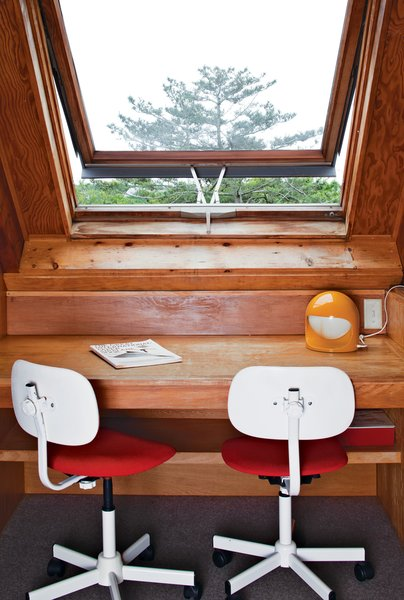 Another of our favorite home office ideas on a budget? Incorporate a basic office space in the upper level or attic of the house, like this small workstation on the upper level of this magnificent, midcentury, A-frame prefab home off the coast of Rhode Island. Here, an airy push-open window provides a refreshing ocean breeze for this sparse workspace.