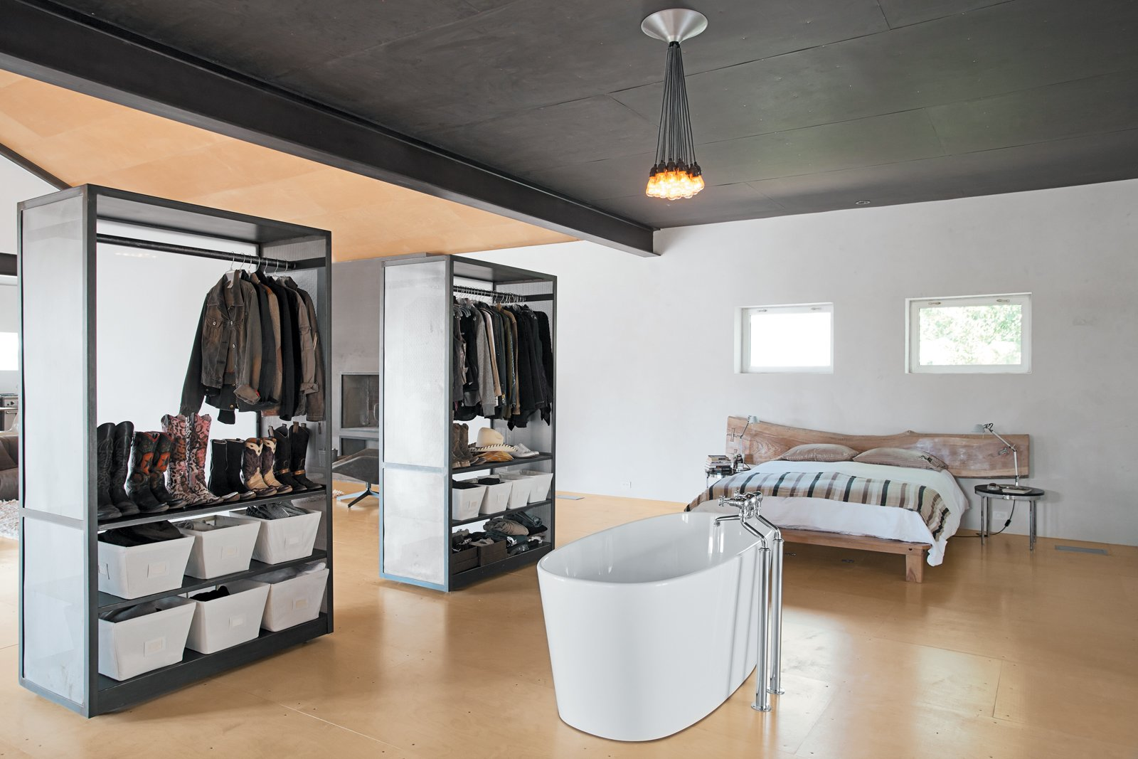 In the bedroom of Barbara Hill's Marta, Texas home, an improbably placed tub is situated in front of two closets that can easily be maneuvered thanks to skateboard wheels affixed to the underside.  Beautiful Bedrooms by Sara Ost