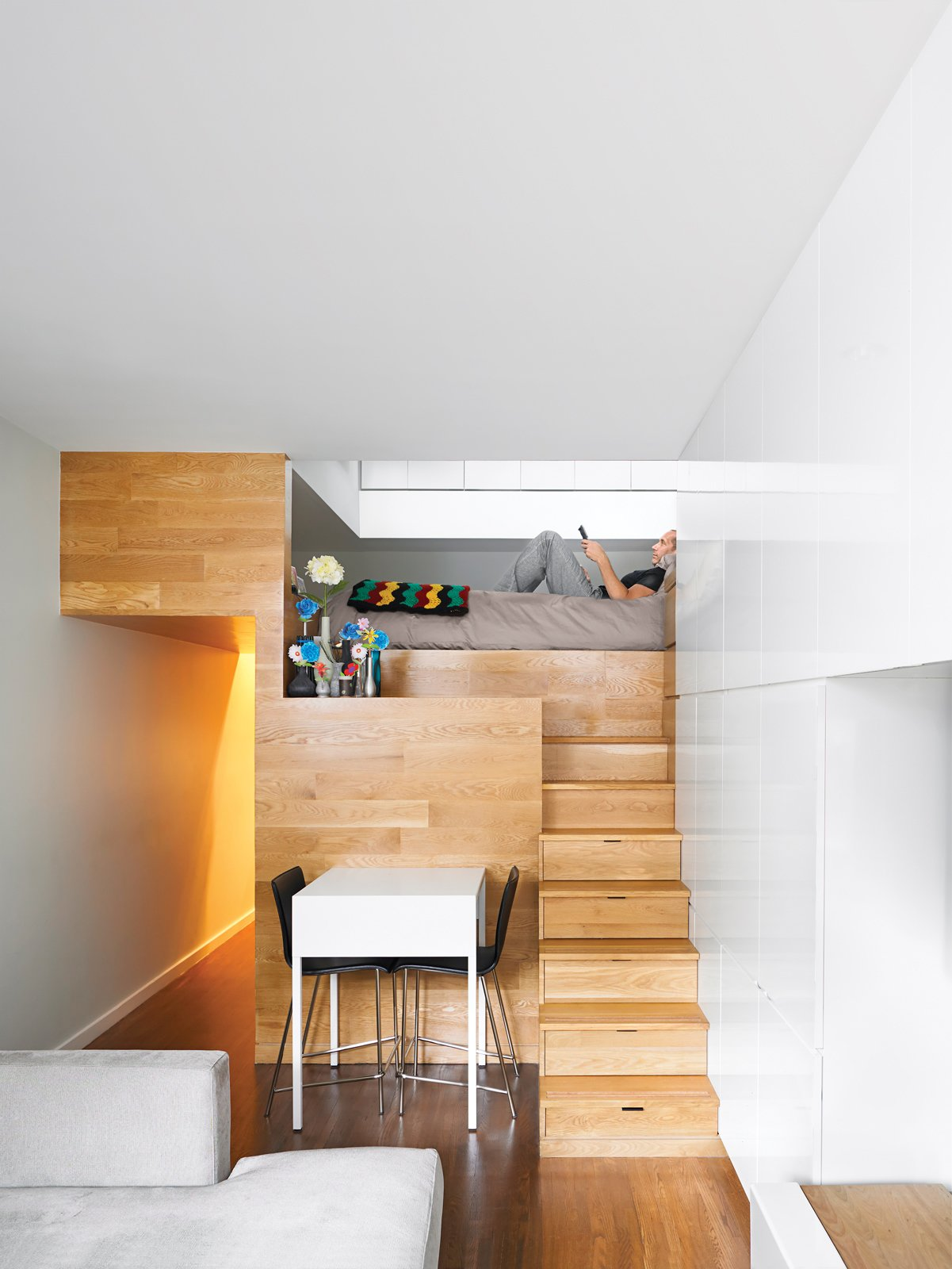 Seven steps doubling as storage drawers lead up to the bedroom of Michael Pozner's not-quite-500-square-foot aerie in Greenwich Village. The bedroom is designed for two people: Both sides of the bed have reading lights and plugs for cell phones and computer chargers.  Bedrooms by Dwell from Beautiful Bedrooms