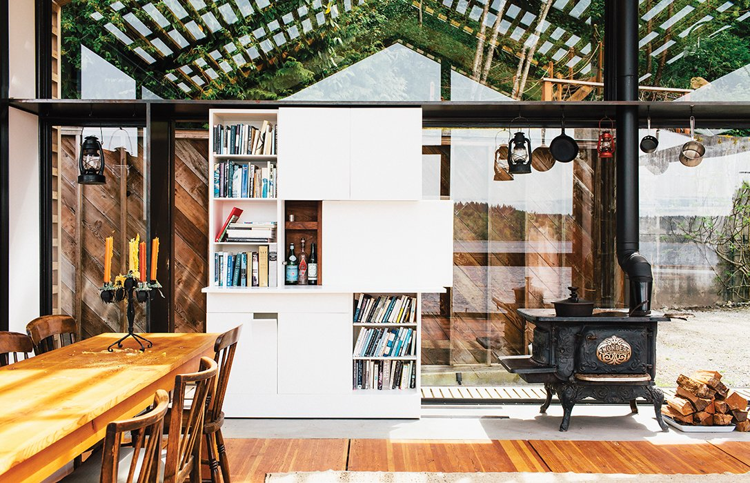 """Dining Room, Storage, Chair, Standard Layout Fireplace, Wood Burning Fireplace, and Table The """"tiny but mighty"""" structure—as Grizzle describes it—packs a wealth of uses into a compact footprint.  Home Libraries that Take Book Storage to the Next Level by Diana Budds from This Renovated Garage is the Ultimate Modern Party Space"""