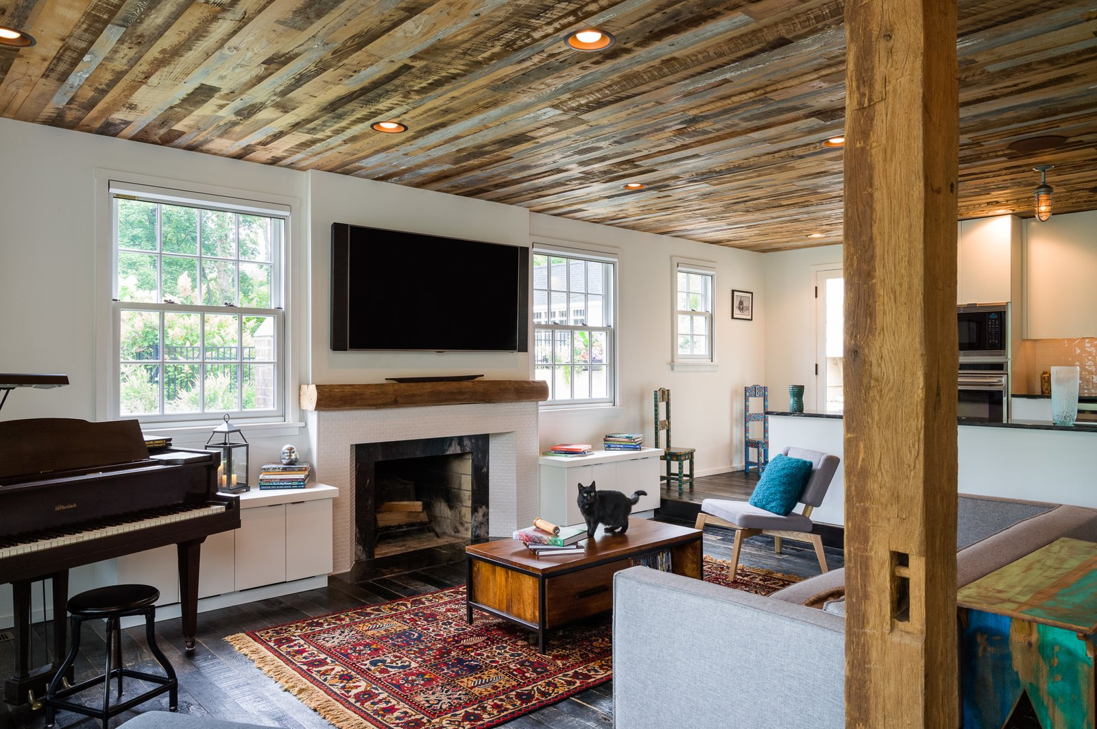 """A few elements of the original home were preserved, such as the brick fireplace in the main living room, where an existing beam was repurposed to act as the mantel. The wood flooring is made of reclaimed fence boards, treated with a black finish originally employed to prevent horses from gnawing on the boards. """"We all walk around barefoot, so it's nice to feel the texture of the wood and all the history that was put into those boards. Over time, the dents and bruises will be put in there by our family, so it's going to weather with us, which is nice,"""" says Michael.  Photo 3 of 8 in A Loving Renovation Updates a Rustic Family Home with Reclaimed Materials"""