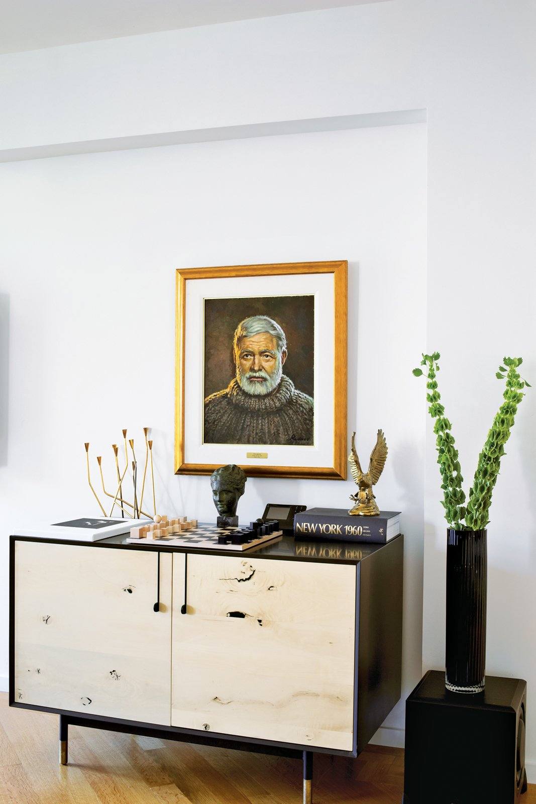 In the living room, a Lake credenza by BDDW is topped with a Bauhaus chess set and a portrait of Ernest Hemingway by the artist Yuriy Rudnev. Tagged: Living Room, Media Cabinet, Light Hardwood Floor, and Storage.  Photo 7 of 9 in A Renovated Flat in Moshe Safdie's Habitat '67