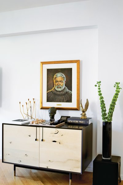 Living Room In the living room, a Lake credenza by BDDW is topped with a Bauhaus chess set and a portrait of Ernest Hemingway by the artist Yuriy Rudnev.  Photo 7 of 9 in A Renovated Flat in Moshe Safdie's Habitat '67