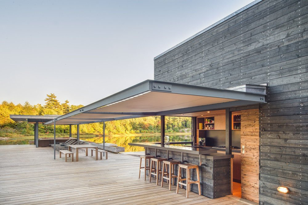 Outdoor, Large Patio, Porch, Deck, and Wood Patio, Porch, Deck A food-service area with a bar is a defining feature.  Photo 2 of 3 in A Modern Lakeside Boathouse in Ontario
