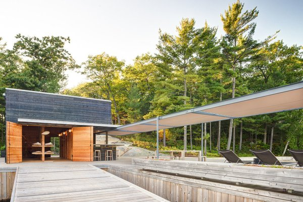 Kayaks and windsurfing equipment are stored in the main cedar-clad volume.