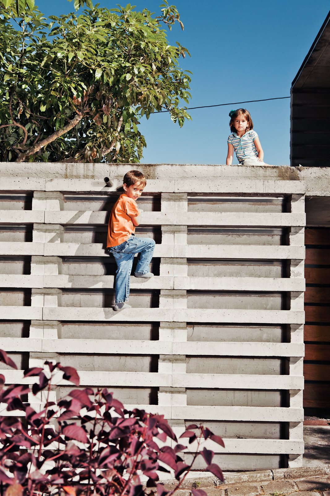 """Outdoor and Concrete Fences, Wall Six-year-old twins Nicolas and Constanza use Pentimento as their """"little battleground,"""" says Pasternak. """"They have some options here that they will not find anywhere else."""" Among those options are a climbing wall offering easy access to the roof.  Photo 6 of 10 in An Innovative Modular Building System in Ecuador"""
