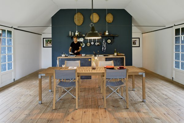 In the kitchen area and throughout the home, Mads Odgård, shown here, and Mette Lyng Hansen mixed Odgård's pieces, such as the Odgård kettle for Raadvad and custom table, with Ikea basics  and the Workshop pendant lamp by Louis Poulsen.