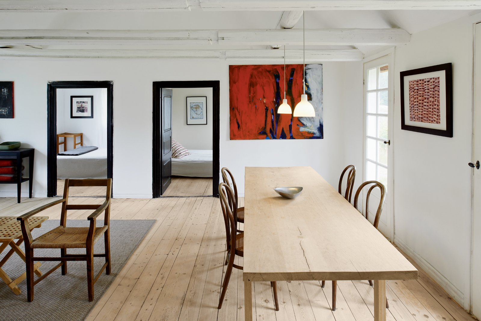 One of the few designer pieces in the home, a set of four Michael Thonet coffee house chairs,  from 1859, offer a simple seating solution. The dining table, designed by Odgård, was built from a 109-year-old oak tree, which was harvested and milled locally.  Photo 2 of 12 in Modern Meets Traditional in a Swedish Summer House