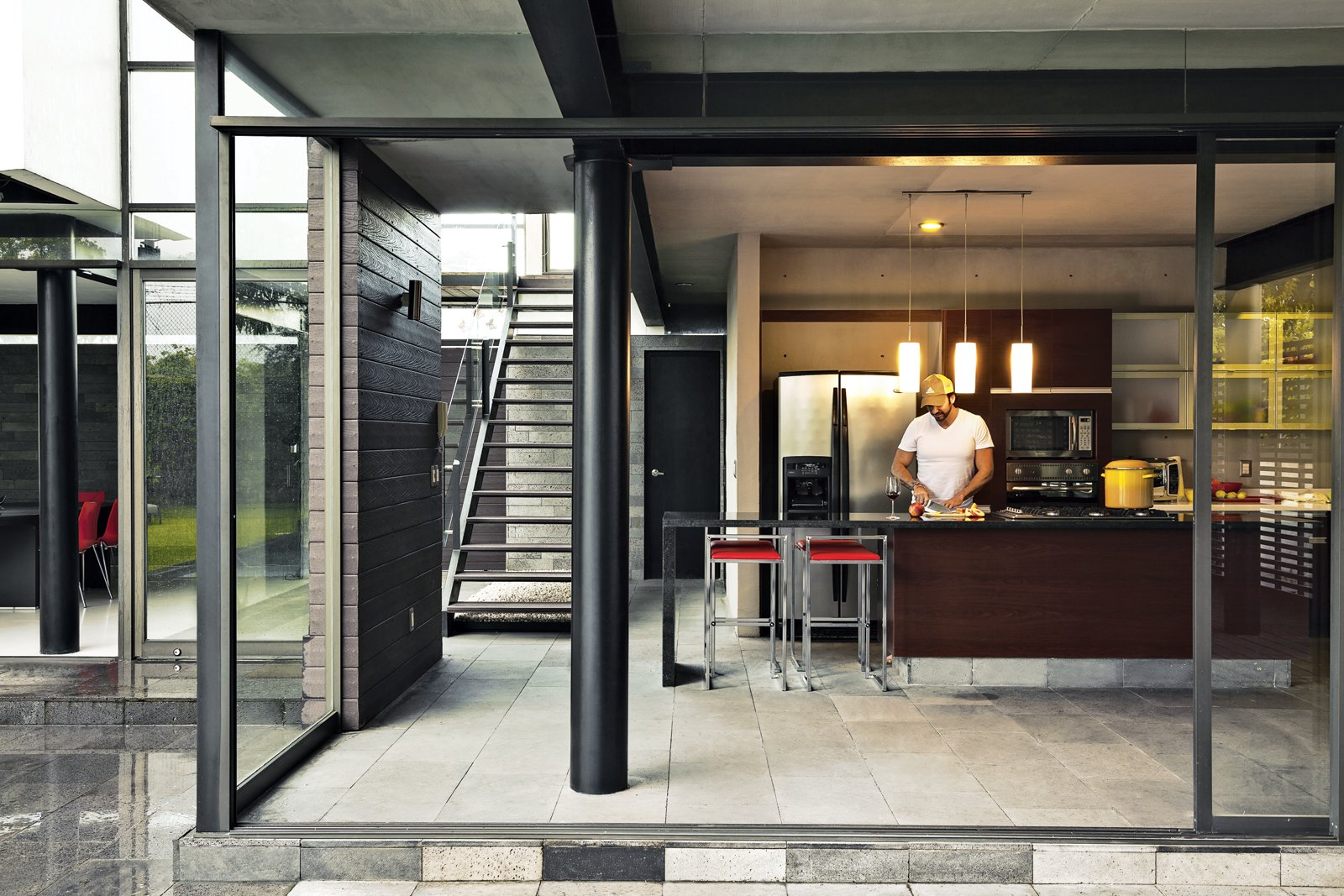 Kitchen, Granite Counter, Refrigerator, Pendant Lighting, and Wall Oven Alfredo chops away in the kitchen, which features floor-to-ceiling sliding glass walls.  Indoor-Outdoor Retreats in Mexico by Allie Weiss from An Affordable High-Design Vacation Home in Mexico