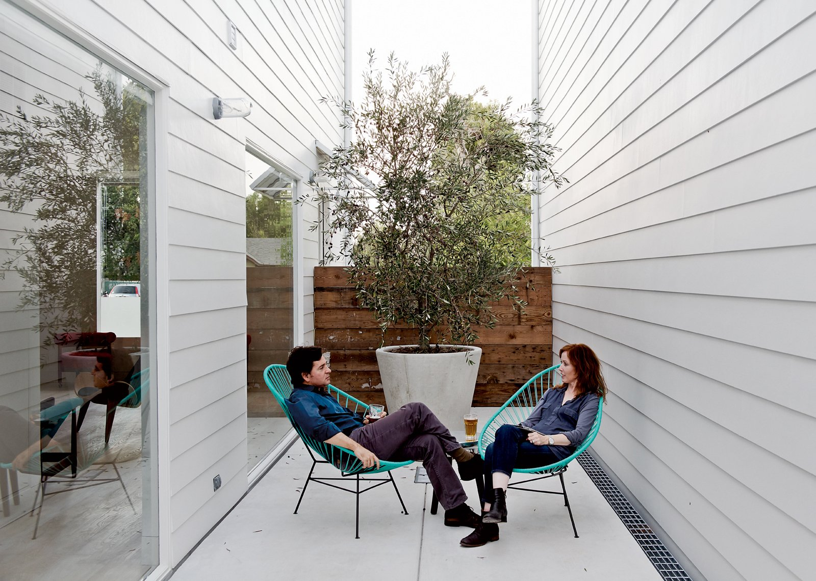 Outdoor, Small Patio, Porch, Deck, and Concrete Patio, Porch, Deck Shannon and his wife, Amy, take the air on a small patio in two Acapulco chairs.  Photo 9 of 15 in Row on 25th: Affordable Housing Development in Houston
