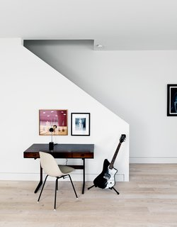 A black electric guitar, a vintage rosewood desk, and a side chair by Charles and Ray Eames sit at the foot of the stairs just beneath a photo of designer Barbara Hill herself competing in the 1956 Miss America Pageant.