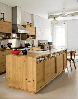 The kitchen of this Brooklyn brownstone features a brick backsplash with a metal panel connecting the Bluestar range to the Viking chimney wall hood. The mashup of materials preserves the personality of brick with the ease of cleaning stainless steel. The island and cabinets are fashioned from remilled Douglas fir beams salvaged from Upstate New York.