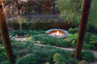 """Made of polished integral concrete with a Cor-Ten steel base, a fire pit """"becomes very much a unique element that sets itself apart in form and color,"""" says landscape architect Stefan Thuilot, who designed it."""