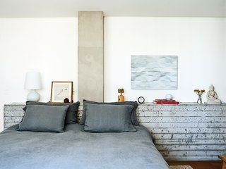 SAO Arquitetura designed the bed and the board-formed concrete headboard in Santos's master bedroom.