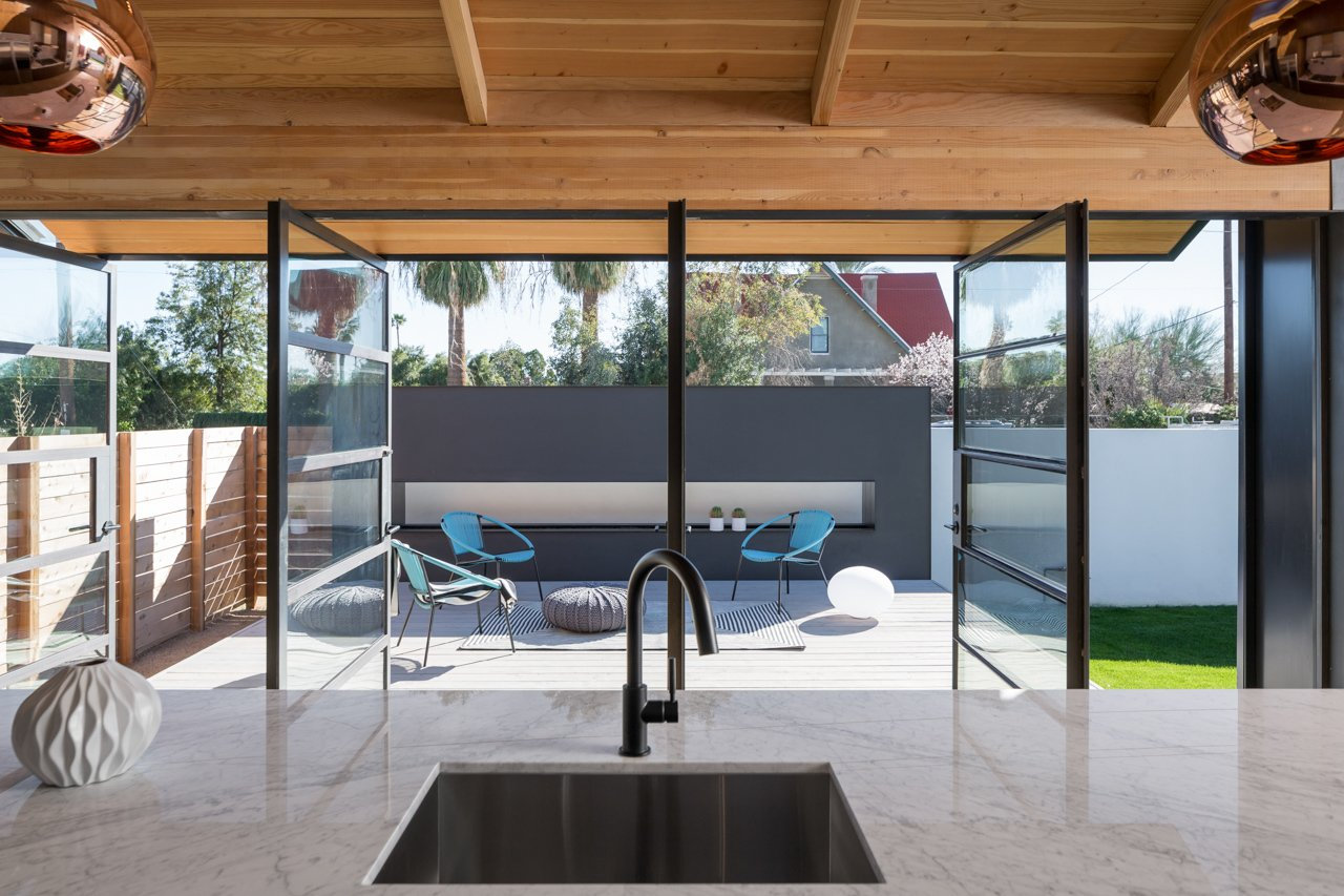 A custom, steel-framed window and door system reinforces the horizontal lines of the existing bungalow. Just outside the kitchen, Contreras can entertain guests on the patio—warmed on chillier days by a low, rectangular fireplace.  Photo 6 of 11 in Amazing House is Half Historic and Half Modern