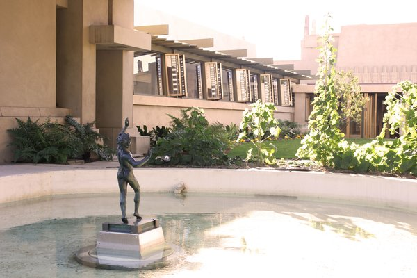A statue stands poised in the middle of a water feature that overlooks the interior courtyard of Frank Lloyd Wright's historic Hollyhock House. The 1920s residence features design representations of the hollyhock plant (a favorite of the original homeowner, oil heiress and avant-garde theater producer Aline Barnsdall), which can be found along the roofline and at the rooftop's corners, as well as in many of the surrounding windows. During the spring months, visitors will have the opportunity to see real hollyhock blossoms displayed in the foreground of Wright's creative designs. The house is now open to the public for self-guided tours, Thursday through Sunday from 11:00 a.m. to 4:00 p.m.
