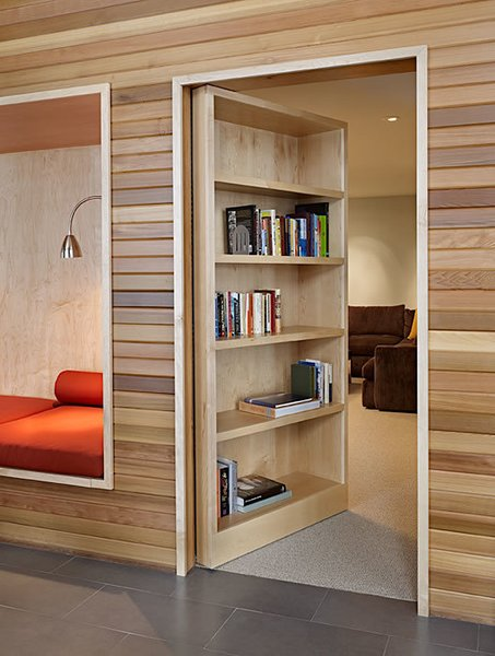With a gentle push, the bookshelf swings open on hinges to reveal a secret media room.