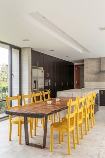 The custom kitchen counters are concrete, and the yellow dining chairs add a welcome splash of color.