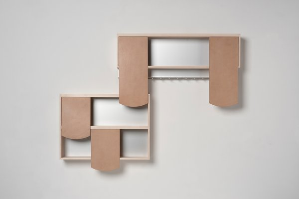 Shingle Shelves by German designer Hanna Kruger playfully suggest the act of opening and shutting cupboard doors—combinable rawhide modules act as sliding doors and overlap like shingles on a roof.