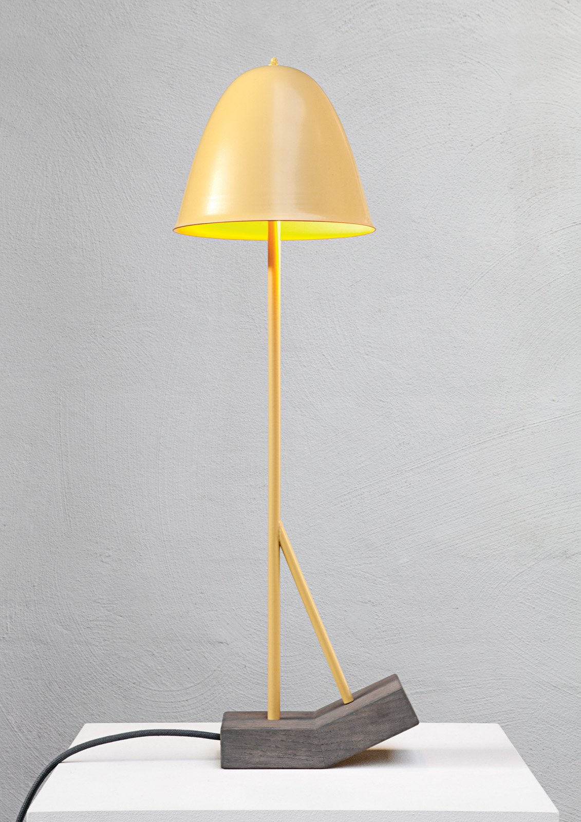 """Pilu by German designer Leoni Werle is a table and a floor lamp in one. An oddly shaped oak base allows the lamp to toggle between two positions. The connection between shade and base is jointed, allowing the beam to be directed downwards even with the lamp is in the angled position.  Search """"f k a table lamp"""" from Emerging Design Talent at imm Cologne"""