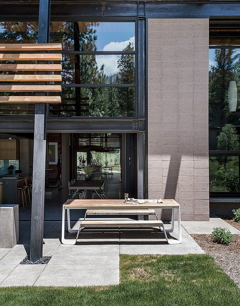"A picnic table from Janus et Cie sits off the kitchen; the landscape architecture is by Richard D. Wood. In addition to passive solar, says Hawkins, ""there is the added benefit of a thick concrete slab as a thermal mass that absorbs and stores the heat from the sun."""