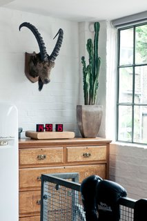 A vintage fridge at the top of the stairs is balanced by modern and industrial touches.