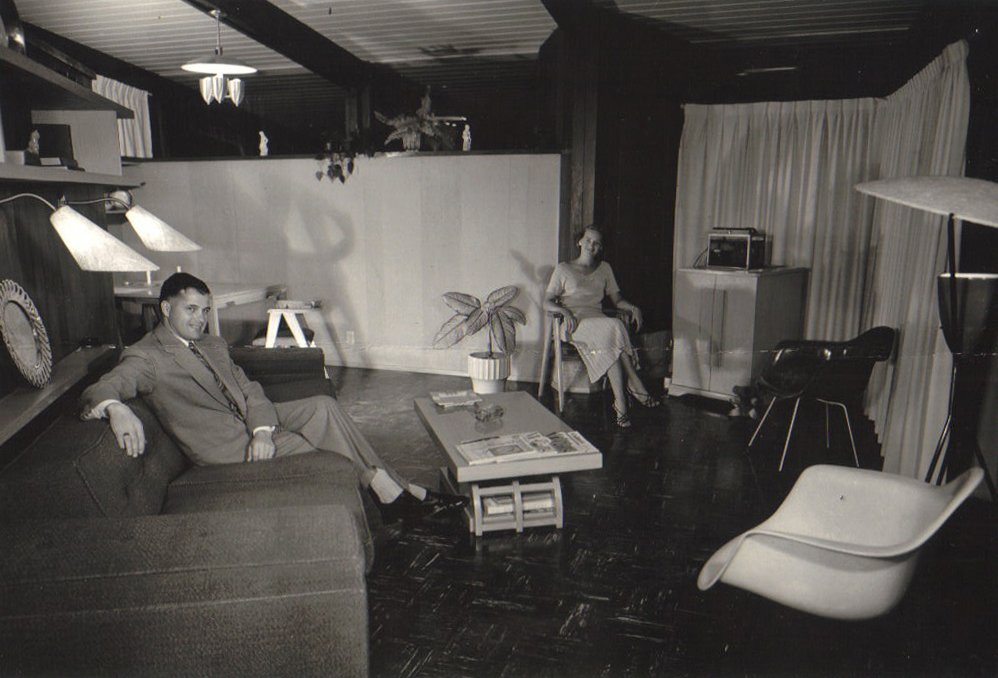 "Roy and Patricia Hamma enjoy time in their living room, furnished with Charles and Ray Eames pieces. Once the couple's MHA 111 model was complete, Roy Hamma, an attorney, hired a professional photographer to document their newly built home, which was one of the original 30 ""guinea pig"" properties.  The MHA cooperative purchased 800 acres of land on the Brentwood side of the Santa Monica Mountains and worked with modernist architects A. Quincy Jones and Whitney R. Smith and structural engineer Edgardo Contini to build 350 homes. Only 85 houses from the original Jones/Smith plans actually saw the light of day.  A New Book on the Los Angeles Development of Iconic Modernist Architect A. Quincy Jones by Brandi Andres"