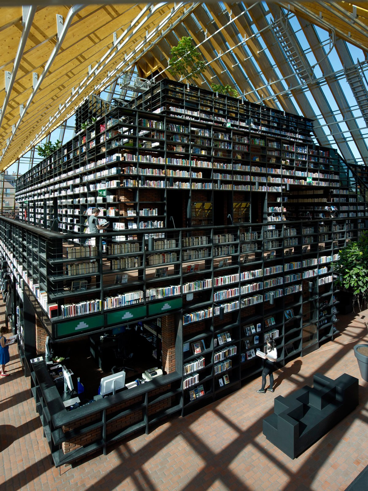 """Architecture: Book Mountain, Spijkenisse, the NetherlandsFor optimum browsing, a veritable mountain of bookshelves created by MVRDV houses over a quarter mile of passages through the structure. Perched at the top is a reading room and cafe area with panoramic views through the transparent roof. Photo by Jeroen Musch.  Search """"mvrdvs balancing barn"""""""" from Contenders for Designs of the Year Announced"""