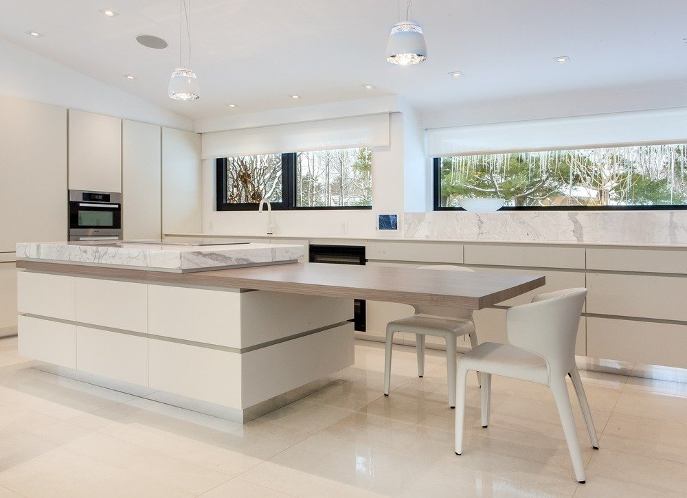 Kitchen and White Cabinet The kitchen features a distinctive cantilevered countertop.  Photo 7 of 7 in Near Montreal, a 1950s House Gets a Modern Makeover