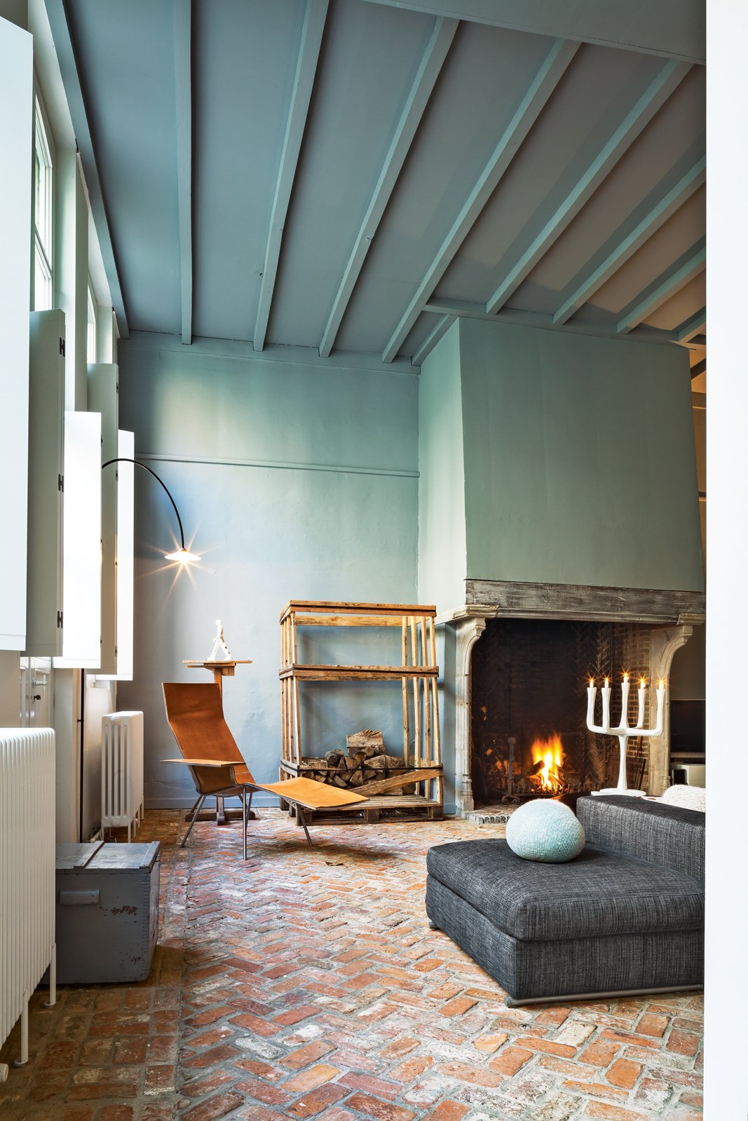 Living Room, Sofa, Chair, and Brick Floor Wenes incorporated artful furnishings into the private spaces: In the living room, a leather chair by Maarten Van Severen is beneath a lamp by his son, Hannes Van Severen, of design duo Muller Van Severen.  Photo 2 of 19 in This House Proves Art Galleries Can Be Super-Friendly