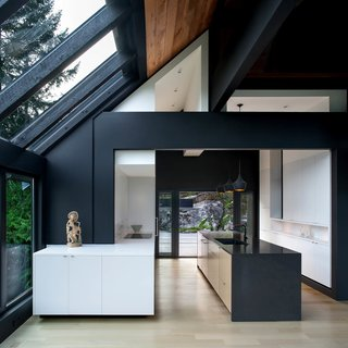 While the house's original pine is richly colored and textured, a number of structural posts rendered the kitchen difficult to furnish with modern fixtures. A newly-added black beam, which extends outward into the dining room, allowed for the posts' removal.