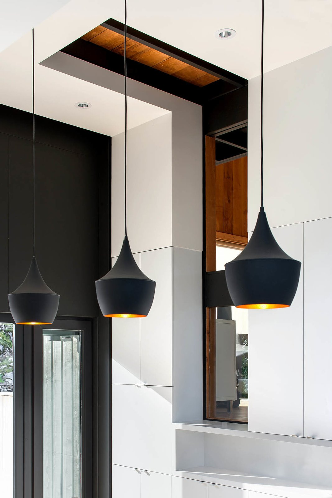 The kitchen faces an elevation, so keeping the space naturally lit was a challenge. The architects specified white surfacing to allow sunlight to bounce off the walls and penetrate the space.  60+ Modern Lighting Solutions by Dwell from A Dramatic Cliffside Kitchen Gets a Sharp and Sculptural Update