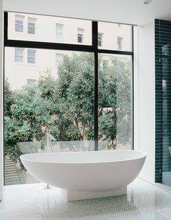 The bathroom features a tub by Benedini Associati for Agape, Dornbracht tub filler, and retractable shades.