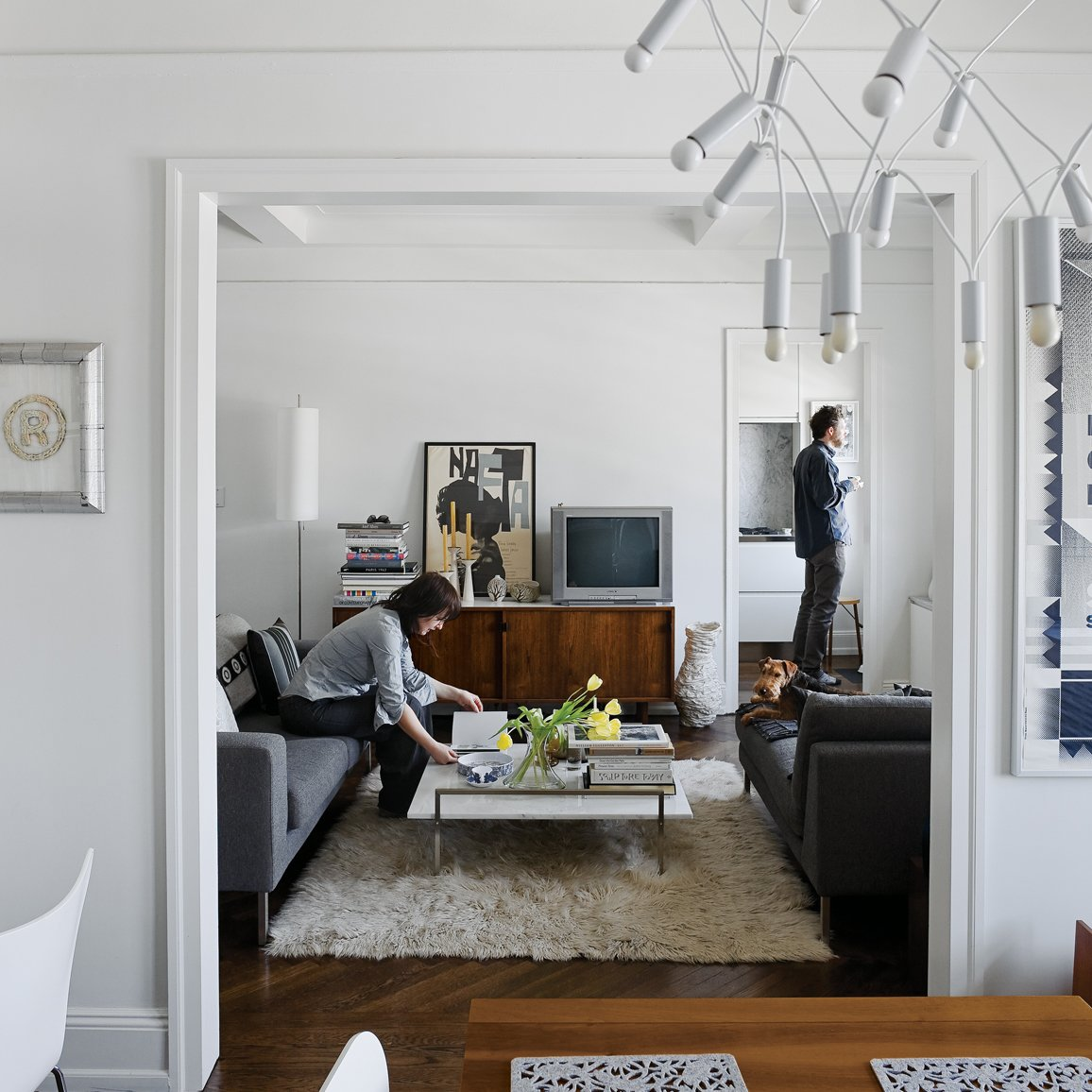 "White lighting elements, finishes, furnishings, walls, and moldings create a feeling of modern openness to this traditional floor plan in New York. Architect Stephan Cassell helped the transplanted couple see past the ""43 layers of paint"" to the modern potential within. ""These old buildings always have interesting layouts that work well,"" Cassell notes, ""and have a certain elegance to them."" See the transformation.  Lounge"