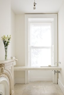 """Architects Anne Marie Lubrano and Lea Ciavarra limited the material selection in their renovation of a town house dating from 1899. The powder room on the first floor is located in a former waiting area (the previous resident used the level for his dental practice). It features a custom Alabastro marble sink and fixtures by California Faucets. The architects kept the original marble fireplace, paying homage to the structure's history. Benjamin Moore's Super White paint was applied to the ceiling and the White Dove hue to the walls. """"Positioning the faucets on the side wall emphasizes the horizontal,"""" Lubrano says. """"Wall-mounted fixtures feel less grounded and materials can continue uninterrupted below. We wanted the spaces to feel light, spacious and light-filled."""""""