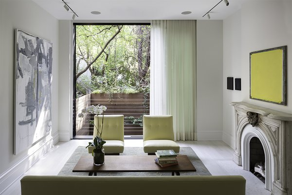 This West Village townhouse integrates the interiors with the outdoor landscape courtesy of floor-to-ceiling windows draped in sheer curtains, which pick up on the hues both inside and out.