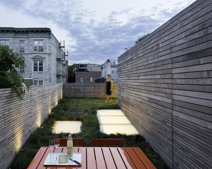 "Outdoor, Rooftop, Horizontal Fences, Wall, Grass, Wood Fences, Wall, and Landscape Lighting A rooftop oasis furthers the outdoor connection. It's planted with red fescue at the client's request for a wild and unmaintained look and an experience akin to ""walking through a field.""  Green Retreats in Bustling Cities by Luke Hopping from A Sophisticated Renovation of a 19th Century Manhattan Town House"
