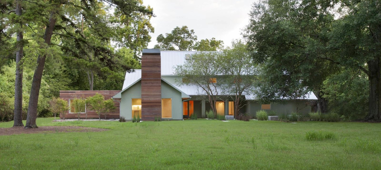 The front elevation reveals two exterior innovations by the architects. Firstly, most Baton Rouge roofs are clad in dark wooden shingles to obscure the mold that will grow in the hot humid climate. This house's metal cladding prevents that growth from occurring while reflecting sunlight and cutting cooling bills. Additionally, a system of exterior ipe slats, with a rainscreen underneath, means the wood will absorb sunlight and keep the additions cool. The ipe will lighten overtime to better match the home's grey exterior.  A Renovation Reconnects a House to its Louisiana Landscape by Zachary Edelson