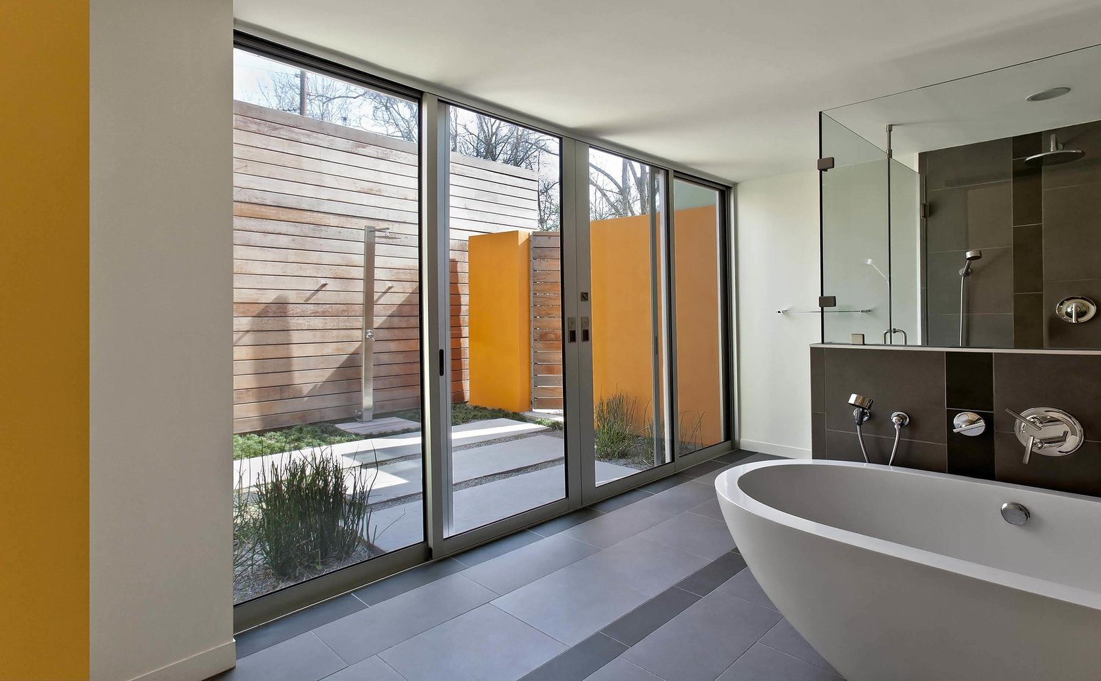 Nestled in between the master bedroom addition and the master bathroom is an outdoor shower. Just as with the kitchen and patio, floor-to-ceiling glazing and continuous concrete pavers blur the barrier between interior and exterior.  A Renovation Reconnects a House to its Louisiana Landscape by Zachary Edelson