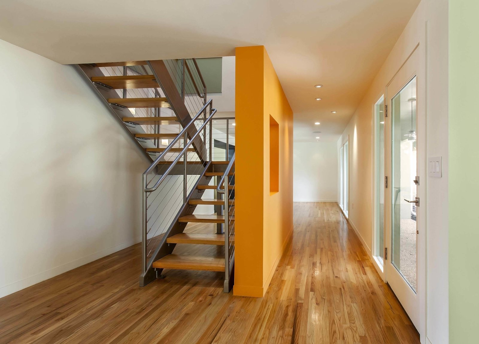 Back in the entry foyer, the architects removed a fully enclosed stair to open up the interior. An operable sunlight just above the stairwell allows hot air to escape, inducing a cooling airflow below and naturally ventilating the space. The space in the image's foreground, located directly adjacent to the kitchen, is now the formal dining area.  A Renovation Reconnects a House to its Louisiana Landscape by Zachary Edelson