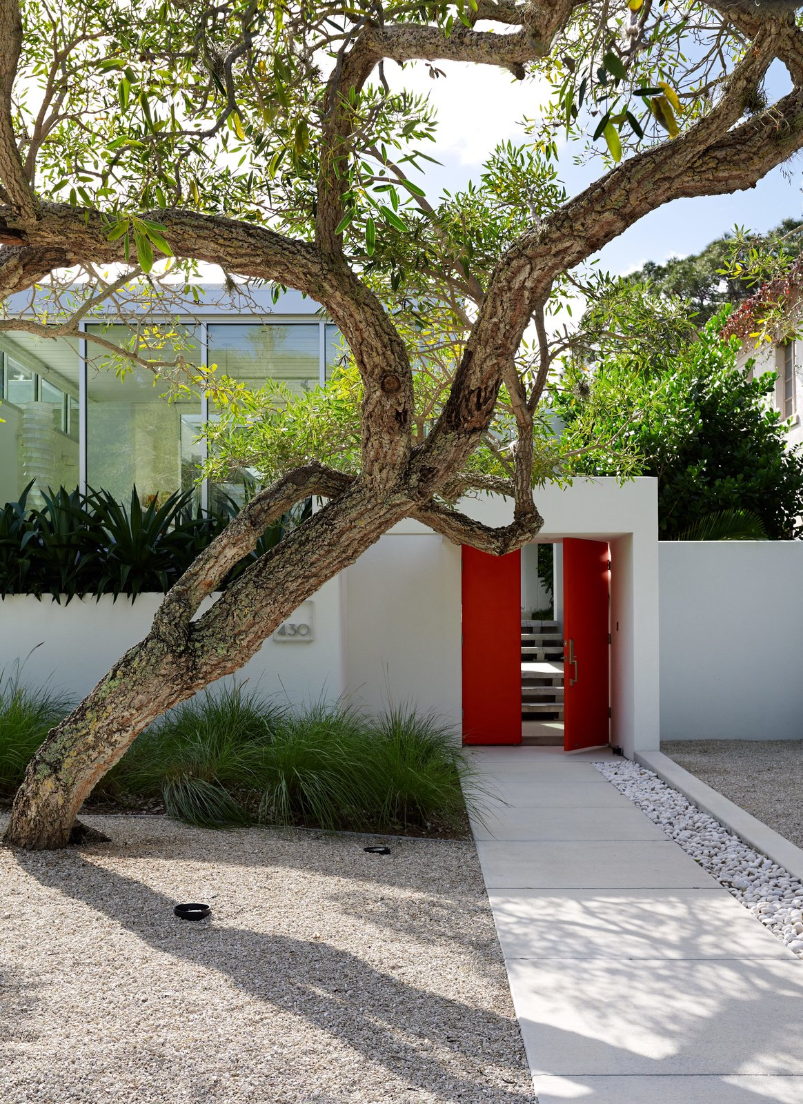"Outdoor, Front Yard, Trees, Hardscapes, and Walkways Benjamin Moore's Tomato Red provides ""punctuation"" to the exterior. ""That was the cheapest way to have that hot spark of color,"" Pirman explains.  Best Photos from This Sparkling New Home Is a Perfect Remake of Classic Sarasota School Modernism"
