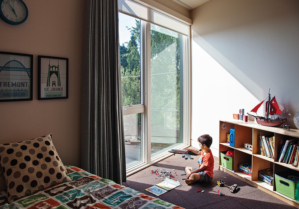 "Kids Room, Bedroom Room Type, Bed, Storage, Carpet Floor, Boy Gender, and Pre-Teen Age ""There are floor-to-ceiling windows in almost every room,"" says Kaja Taft of her prefab home in Portland. ""Light was a big part of why we loved this design."" With so much light comes the need to block it out at times, especially in the children's rooms. Though the couple invested in solar shades and blackout curtains by Mari Design, ""They still get up at 5:30,"" Kaja says with a laugh. As in all the bedrooms, the carpet tiles are from Flor.  Photo 5 of 12 in 28 Triangles Make Up This Hyper-Angular Family Home"