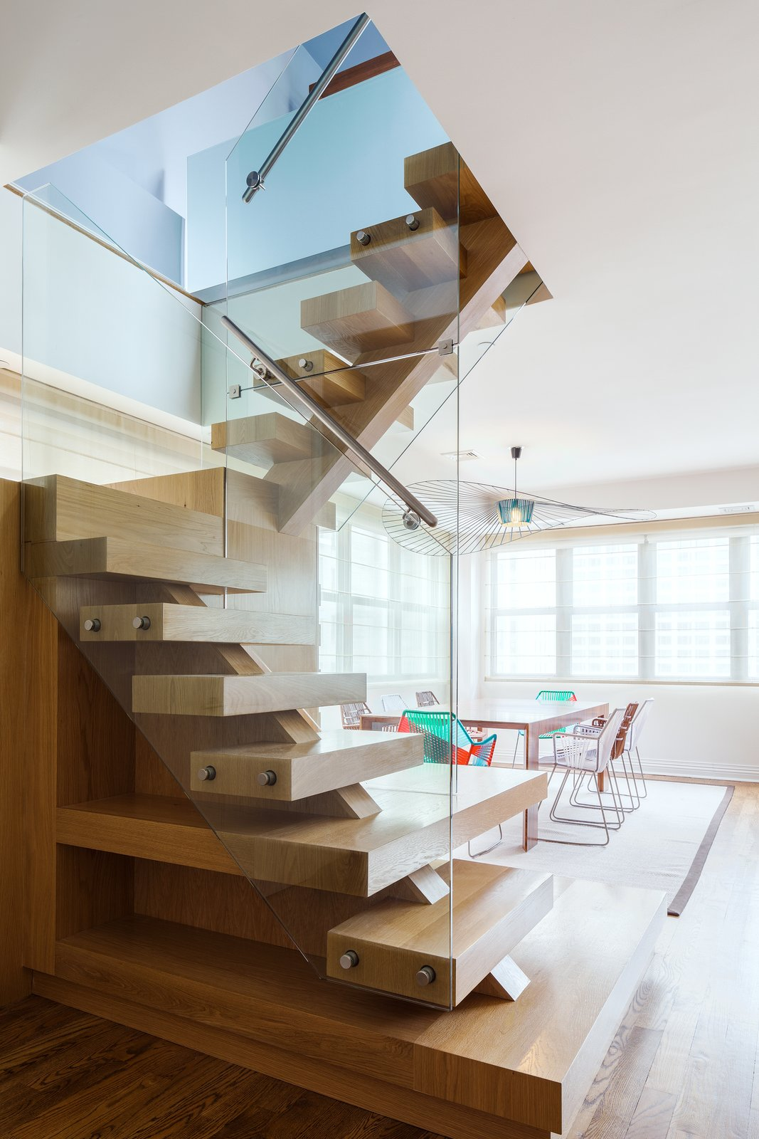 Staircase, Wood Tread, and Metal Railing Reddy swapped out the spiral iron staircase for a modern wood one protected by glass walls.  Lovely NYC Abodes That Will Give You Apartment Envy by Allie Weiss from Super Sleek Staircases