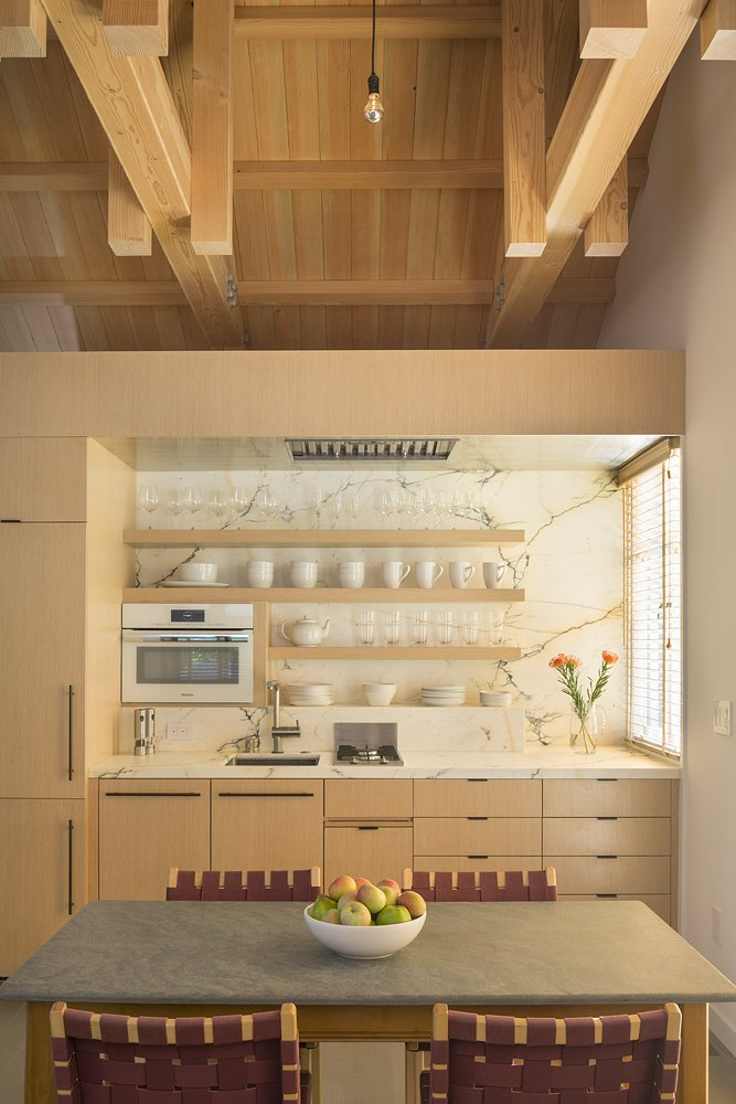 "Richardson centered the renovation on a space-efficient ""service cube,"" an eco-wood box that houses a marble kitchen and a bathroom. The dining chairs are by Jens Risom.  Kitchen from A Small Loft Sits Above a Renovated Barn in California"